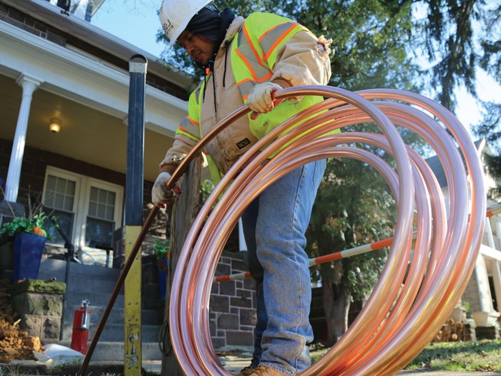Photo of a worker installing copper pipe